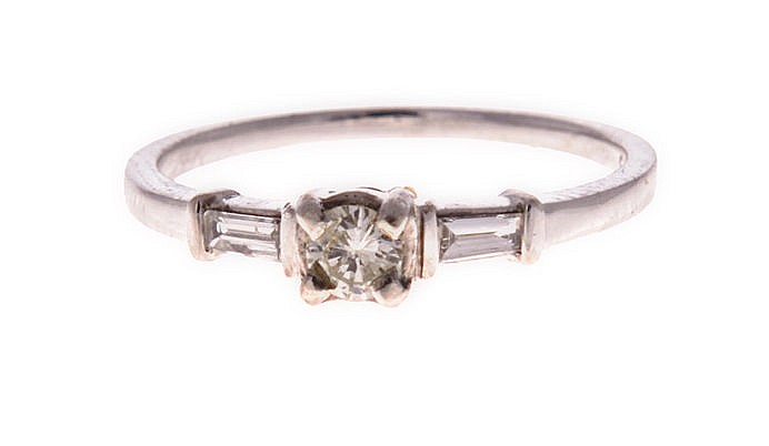 A DIAMOND RING centred with a tinted white round brilliant-cut diamond weig