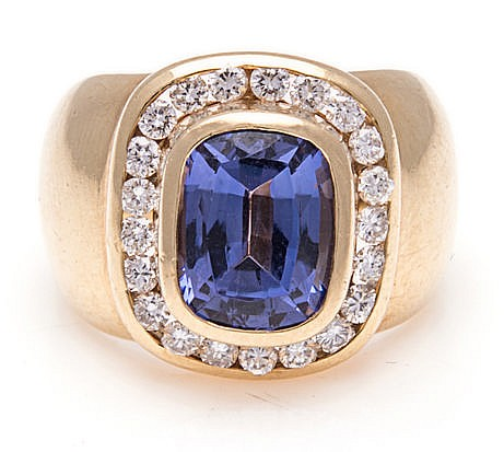 A TANZANITE AND DIAMOND RING, JENNA CLIFFORD centred with a bezel-set cushi