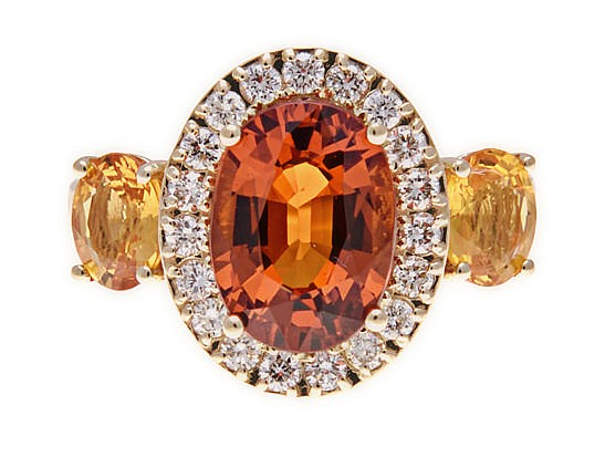 A SPESSARTITE GARNET, DIAMOND AND YELLOW SAPPHIRE RING claw-set to the cent