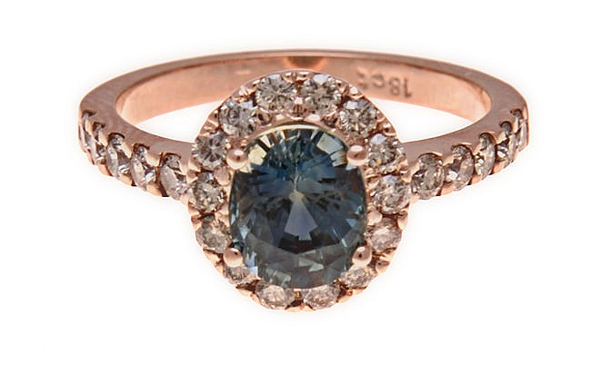A SAPPHIRE AND DIAMOND RING centred with an oval mixed-cut sapphire weighin