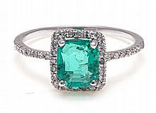 AN EMERALD AND DIAMOND RING centred with a square