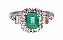 AN EMERALD AND DIAMOND RING centred with a claw-se