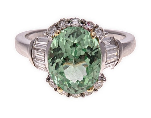 A TSAVORITE AND DIAMOND RING centred with an oval mixed-cut tsavorite weigh
