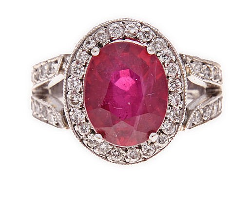 A RUBY AND DIAMOND RING claw-set to the centre with an oval mixed-cut fract