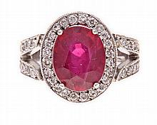 A RUBY AND DIAMOND RING claw-set to the centre wit