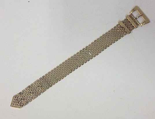 A 9CT GOLD BRACELET comprised of nine rows of brick links, with an adjustab