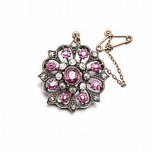 A RUBY AND DIAMOND BROOCH of circular form, centred with an oval mixed-cut