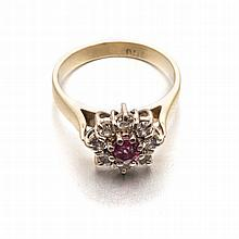 A RUBY AND DIAMOND RING of flower design, centred with a circular ruby weig