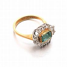 AN EMERALD AND DIAMOND RING centred with a bezel-set emerald step-cut emera