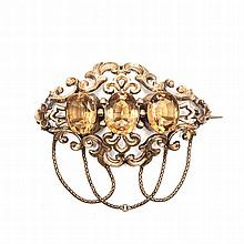 A CITRINE AND DIAMOND BROOCH/PENDANT composed of openwork scrolls, centred