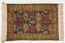 A HEREKE SILK RUG, TURKEY, MODERN the field with overall cartouches in red,