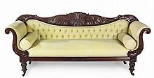 A REGENCY MAHOGANY SETTEE the foliate-carved top rail above a padded button