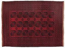 AN AFGHAN CARPET, CIRCA 1960 the red field with three rows of seven guls de