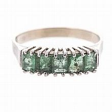 AN EMERALD AND DIAMOND RING claw-set with five emerald-cut emeralds weighin
