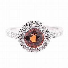 A MANDARIN GARNET RING centred with a mixed-cut mandarin garnet weighing ap