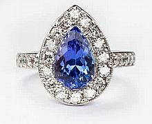 A TANZANITE AND DIAMOND RING centred with a pear-shaped mixed-cut tanzanite