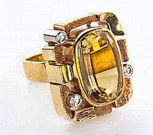 A GOLD DRESS RING centred with an oval mixed-cut citrine, the surround comp