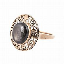A GOLD RING centred with an oval cabochon black stone, within a conforming