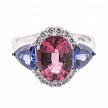 A PINK TOURMLAINE, TANZANITE AND DIAMOND RING centred with an oval mixed-cu