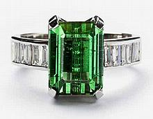 A GREEN TOURMALINE AND DIAMOND RING centered with a claw-set lozenge-cut gr