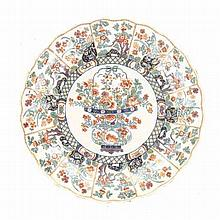 A DELFT POLYCHROME AND ENAMELLED PLATE scalloped rim, centred by a flowerhe