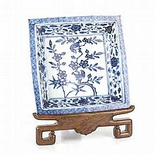 A CHINESE BLUE AND WHITE DISH, QING DYNASTY, 19TH CENTURY square, on a carv