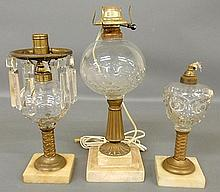 Three oil lamps with clear glass fonts, brass shafts and alabaster bases, tallest 15