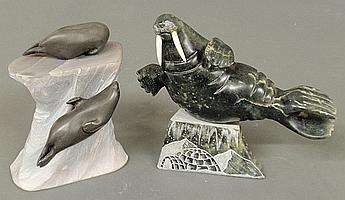 Two Inuit carved stone sculptures- two seals mounted on a light grey stone base signed
