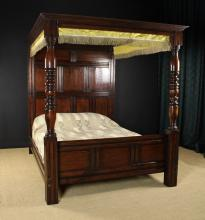 An Oak Full Tester Bed in the 17th Century Style.  The tester composed of two sections of panelling contained within the moulded cornice and raised on turned foot posts and a panelled head board. The head board having two upper panels over three mid panels and four base panels in a run moulded framework. The foot posts leading down to square block legs united by a triple panelled foot board. The mattress on slatted supports. 78½ ins (200 cms) high, 65 ins (165 cms) wide, 86 ins (219 cms) in length.