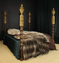 A Fine 19th Century Portuguese Carved & Partially Gilded Four Poster Bed.  The posts surmounted by crested finials and enriched with carved scrollwork, swagged drapery and pendant bell flower heads, above spiralling columns entwined with platted stems. The square block feet united by rails, with replacement pine splats supporting the mattress. 78¾ in (200 cm) in height.