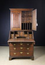 An 18th Century Oak Bureau Bookcase. The top section having a moulded cornice above two arched fielded panel doors, opening to reveal shelves and letter racks. The bureau having a lip moulded fall front enclosing a stepped interior of drawers and pigeon holes flanking a central cupboard and secret compartments concealed behind half column pilasters. The two short and three long cock-beaded drawers below standing on bracket feet, 76 ins (193 cms) high, 36 ins (91 cms) wide.