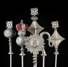 Six Antique Pewter Ceremonial Staff Heads; to include one in the form of an orb surmounted by a coronet with a cushioned crimson velvet insert, 16 ins (41 cms) in height, one as a double sided sunburst face mask 16½ ins (42 cms) in height, one as a crozier, etc.