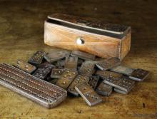 A Late 19th Century Leather Domino Set fitted in a rectangular tooled leather case with a punched score board 5½ ins (14 cms) in length, 1½ ins x 1¾ ins (4 cm x 4.5 cms).