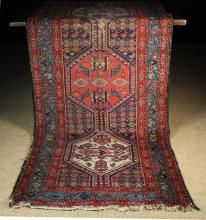An Antique Caucasian Wool Runner woven in red, mid blue, dark blue and ivory wools with linked red and ivory ground hexagons of geometric figural motifs in a banded border, 195 ins x 39 ins (496 cm x 100 cms).