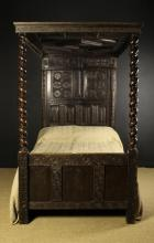 A 19th Century Oak Bed in the 17th Century Style. The tester with geometric moulding incorporating panels of incised lozenge and ball flower motifs. The panelled head board carved with the date 1686 and enriched with daisy wheels in guilloche bands above four chip carved base panels. The turned double-bine foot posts spiralling down to a triple paneled foot board, 80 in (203 cm) high, 77 in (196 cm) in length, 48 in (122 cm) wide.