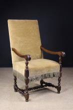 A Late 17th/Early 18th Century Louis XIV Walnut Fauteuil.  The upholstered rectangular back and padded seat covered in a golden fawn velvet edged in a metallic gold fringe.  The scroll end arms on turned inverted cup knopped supports leading down to similarly turned legs united by a high turned front stretcher and conforming H-form under-stretcher. 45 ins (14 cms) high, 24½ ins (62 cms) wide.