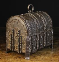 A Fine 15th Century French Wrought Iron Dome Topped Casket , clad in decorative cross-hatched straps adorned with faceted square studs alternated with bands of intricate tracery. The lid centred by an oval ring handle. The base having two pins to the corners releasing spring loaded hasps to the front, 7¼ ins (18.5 cms) high [handle down], 8 ins (20 cms) wide, 5½ ins (14 cms) deep.