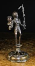 An Antique Bronze Gothic Style Figural Candlestick of dark brown patination. The mediaeval male figure holding a branch entwined with a serpent in one hand with a hexagonal candle socket in the other, raised on a small platform above a pierced sexfoil base, 10½ ins (27 cms) high,