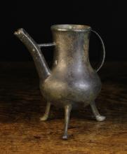A Rare 14th Century Bronze Ewer. The pot-bellied vessel raised on three footed legs with a strap handle to one side and a spout with cross bracket to the other, 8 ins (20 cms).