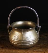 A Small 16th/17th Century Bronze Cauldron with iron swing handle looped through triangular lugs either side, oval medallions cast with initials and a ringed frieze bands, 4¾ ins (12 cms) high [handle down]. 5½ ins (14 cms) in diameter.