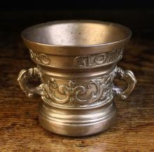 A 17th Century Bronze Mortar cast with date and inscription around the rim; SOLI DEO GLORIA 1629, above a frieze band of scrolling foliate motifs and dolphin form handles, 4 ins (10 cms) in height, 4¼ ins (11 cms) in diameter.