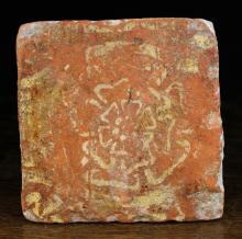 A 16th Century Terracotta Tile decorated with a Tudor rose, 5 ins (13 cms) square.