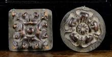 Two Small Carved Wooden Bosses mounted on lead plaques: a Tudor rose 3 ins (8 cms) in diameter, and a quatrefoil 3 ins (8 cms) square.*