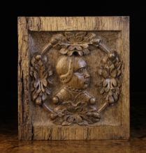 A Small 16th Century Oak Panel carved with a profile of a woman's head in a ring adorned with clusters of leaves and fruit. The recessed ground stamped with punchwork, 10 ins x 9 ins (25.5 cm x 23 cms).