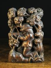 A 16th Century Relief Carved Oak Panel depicting a huntsman knelt amongst trees aiming a crossbow, 8¾ ins x 5½ ins (22 cms x 14 cms).