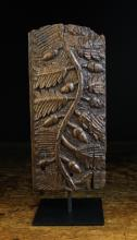 A 17th Century Carved Oak Frieze Fragment. The rectangular panel decorated with an undulating stem of oak leaves and acorns, 11 ins x 5 ins (28 cm x 13 cms), mounted on a modern display stand.