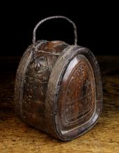 An 18th Century Chip Carved Wooden flask bound in iron straps and fitted with a wrythen iron swing handle to the top. The coopered sides and tear drop ends naively carved with flower motifs, scrolls and ropetwist bands, incorporating the initials OAS to one side and further initials Eit with date 1730 to the base, 6¾ ins x 5½ ins x 4½ ins (17 cm x 14 cms x 11.5 cms).+