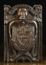 A Fine 16th Century Carved Oak Beam Angel bearing a Heraldic shield, 14½ ins x 9 ins (37 cm x 23 cms).