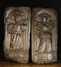 A Pair of 16th Century Naively Carved Oak Panels. Each depicting a saint stood in an arched niche, holding a monstrance, 18 ins x 8 ins (46 cms x 20 cms).