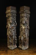 A Pair of Renaissance Carved Oak Figural Corner Posts. The bare-breasted female figures representing fertility, depicted scantily clad in draped robes with a child stood at their side and an abundance of fruit and foliage upon their heads, 23 ins (64 cms) high, 6 ins (15 cms) in width.*